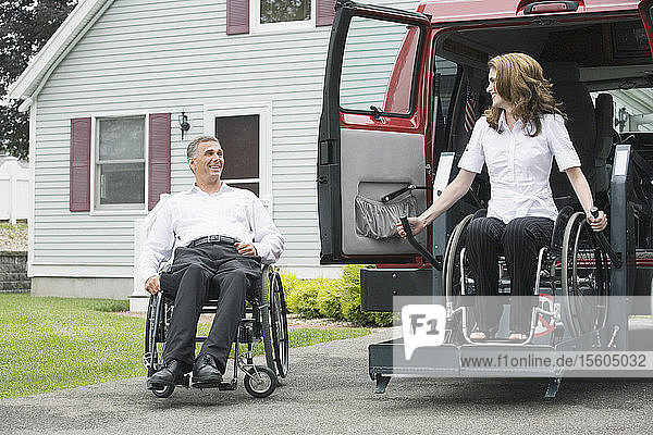 Mature man sitting in a wheelchair with a Spinal Cord Injury and looking at a mid adult woman with a Spinal Cord Injury being lowered from a wheelchair lift