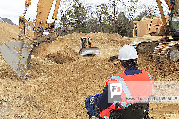 Construction engineer with spinal cord injury inspecting new foundation hole