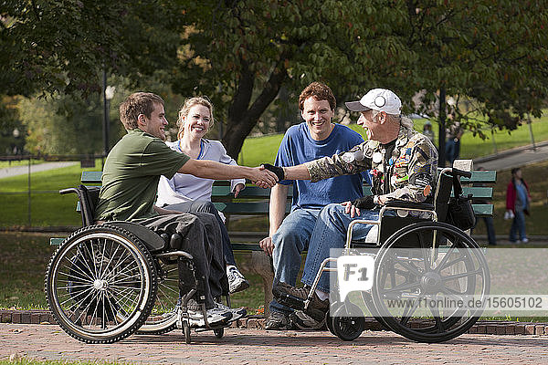 Veterans joining friends and shaking hands in the park