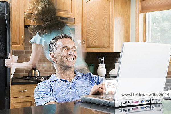 Mittlerer Erwachsener  der in einem Rollstuhl sitzt und einen Laptop benutzt  während eine mittlere erwachsene Frau hinter ihm geht