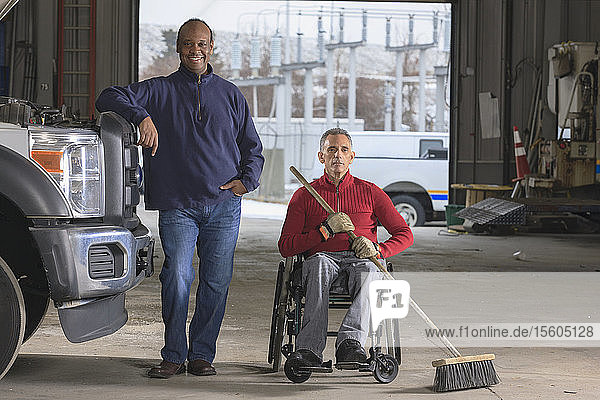 Maintenance technicians  one with a spinal cord injury  cleaning in utility truck garage at Electric Power Plant