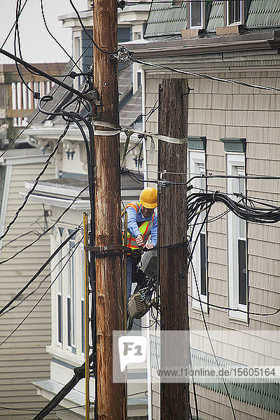 Cable lineman on ladder trimming wiring on city power poles
