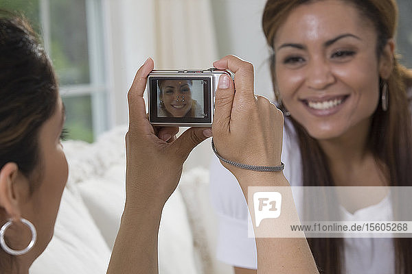 Hispanic woman taking a picture of her friend