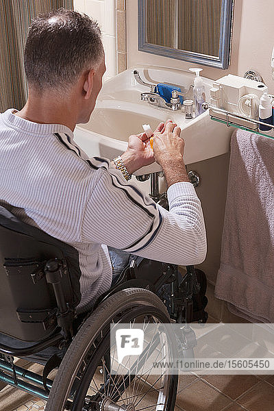 Man with spinal cord injury in a wheelchair taking medicines