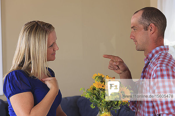 Husband with flowers signing 'For You' and his wife signing 'For Me' in American sign language both with hearing impairments