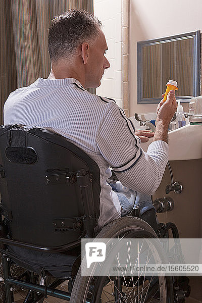 Man with spinal cord injury in a wheelchair looking at a pill bottle