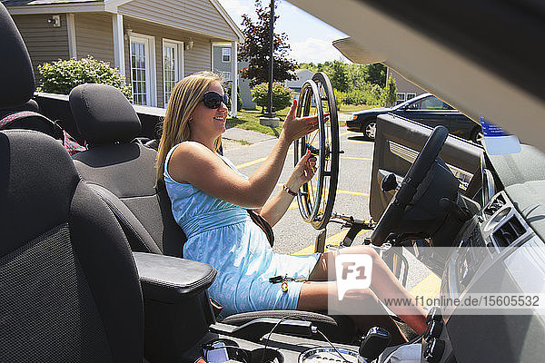 Woman with spinal cord injury pulling wheel from wheelchair into her adaptive vehicle