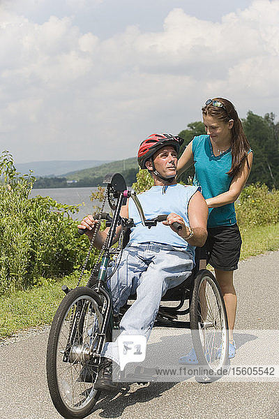 Young man with a Spinal Cord Injury riding adaptive bike with a young woman standing behind him and smiling