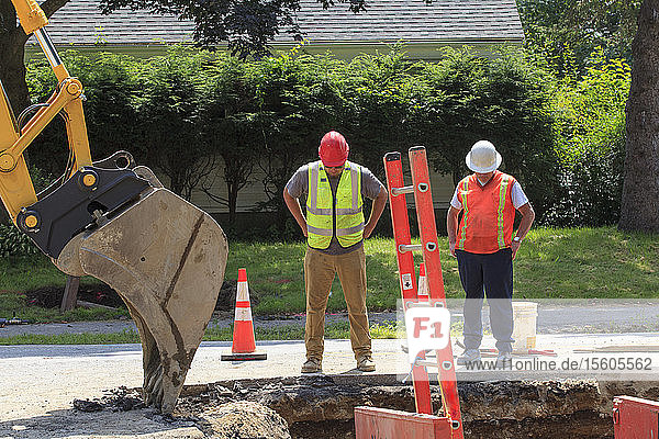 Construction worker and inspector viewing water main installation