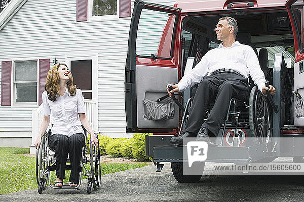 Mid adult woman sitting in a wheelchair and looking at a mid adult man being lowered from a wheelchair lift with a Spinal Cord Injury