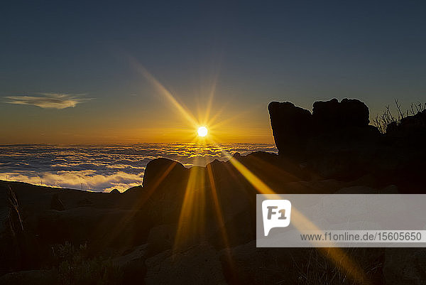 Haleakala at sunset with dramatic golden sun rays shining bright over rock and clouds; Maui  Hawaii  United States of America