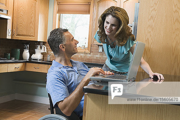 Mid adult man sitting in a wheelchair at a kitchen counter and using a laptop with a mid adult woman standing beside him smiling
