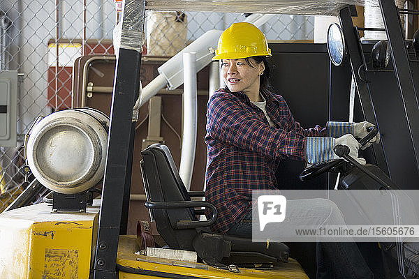 Female power engineer driving a forklift truck in service garage