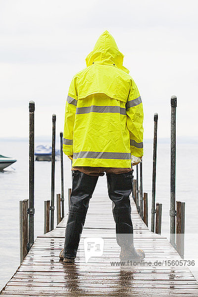 Public works engineer on dock carrying water sample packet from lake