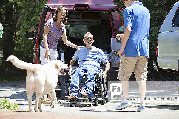 Man with spinal cord injury exiting an accessible van to see his family