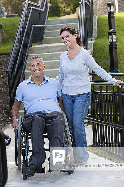 Woman standing with husband in wheelchair with spinal cord injury on accessible ramp