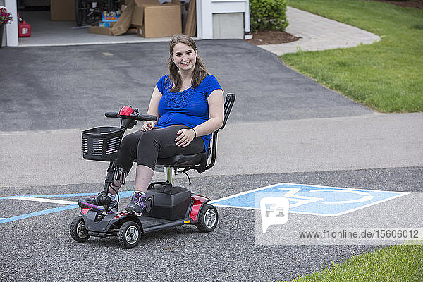 Young Woman with Cerebral Palsy in her scooter with disability parking