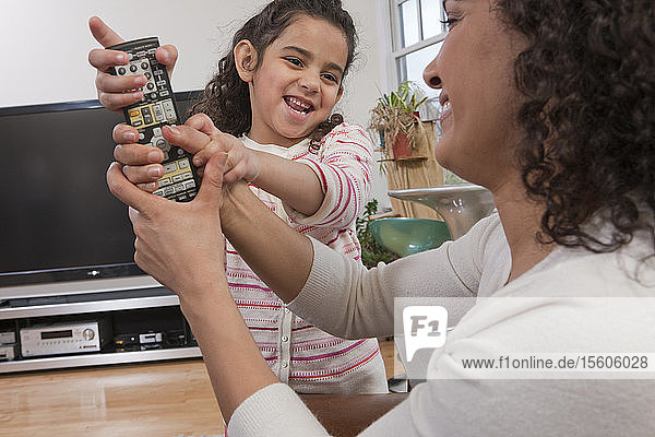 Hispanic girl pulling remote control away from her mother