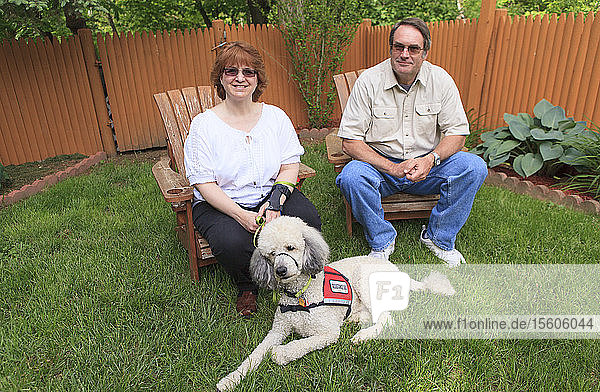 Woman with RSD and her service dog with husband sitting in their back yard