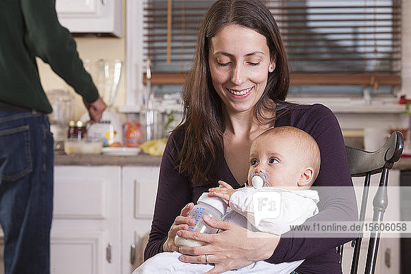 Baby in mother's arm with pacifier and father making lunch