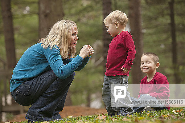 Woman signing the word 'Hurt' in American Sign Language while communicating with her son in a park