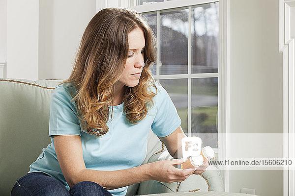 Woman at home looking at pills bottles