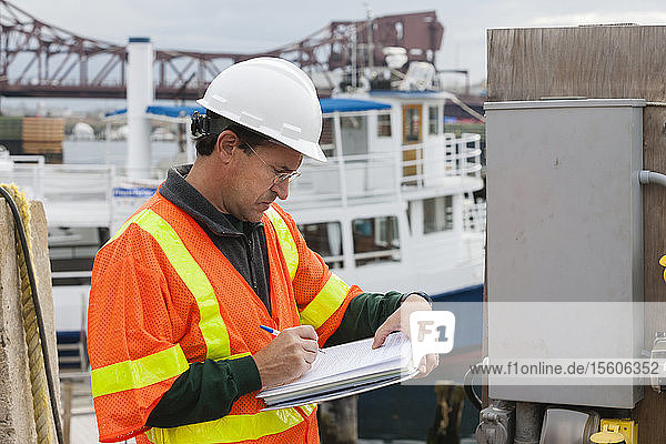 Environmental engineer recording data at ship side in harbor