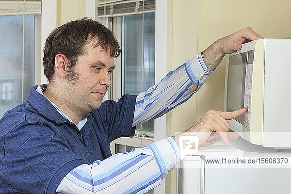 Man with Asperger's living in his home and cooking in microwave