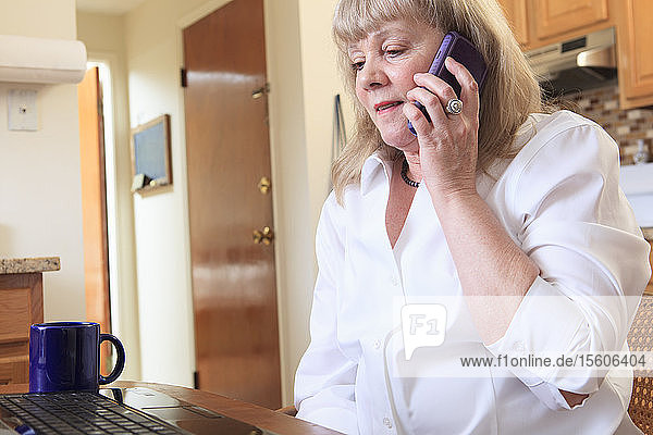 Woman with Bipolar disorder working from home on her laptop with phone