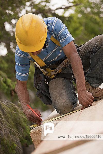 Carpenter using tape measure on flooring