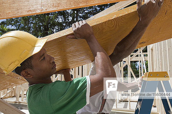 Carpenters lifting a laminated beam at a construction site