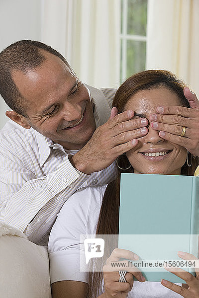 Hispanic man covering a woman's eyes from behind