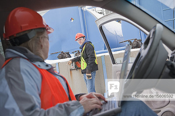 Engineer using a laptop in truck with an another engineer inspecting site