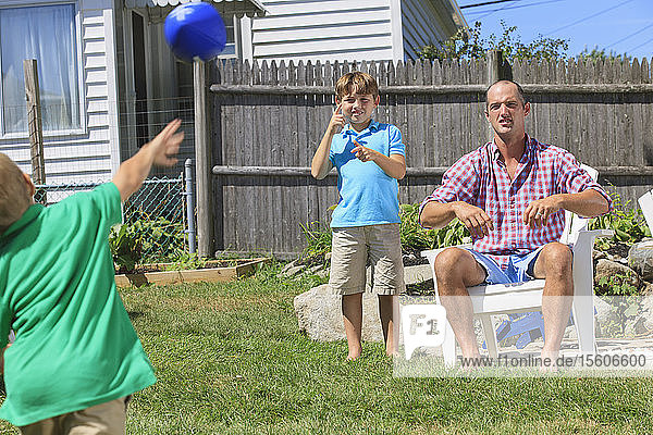 Father and sons with hearing impairments playing football and signing 'brother' in American sign language in backyard