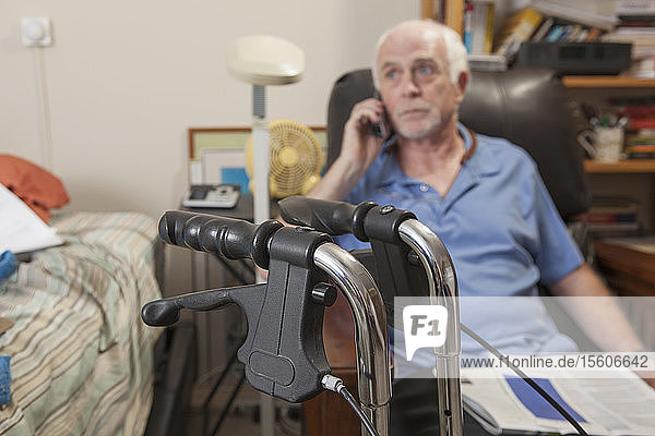 Man with Ataxia with his walker and talking on his cell phone in his bedroom