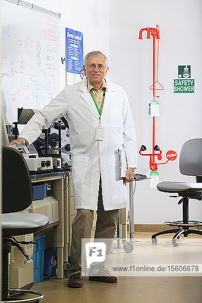 Professor standing beside x-ray fluorescence equipment and safety shower and eye wash station in chemical analysis lab