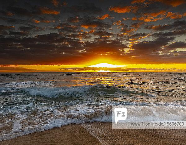 Bright  golden sunrise over beach and ocean; Kauai  Hawaii  United States of America