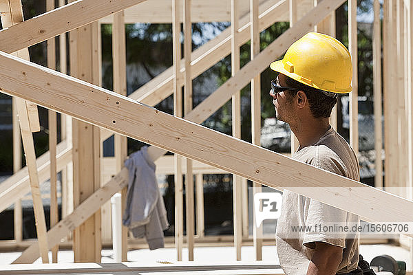 Carpenter standing under a framed house