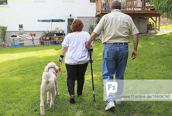 Woman with RSD and her service dog with husband walking in their back yard
