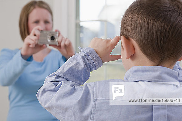 Boy signing the word 'Picture' in American Sign Language while his mother taking a picture of him with a digital camera