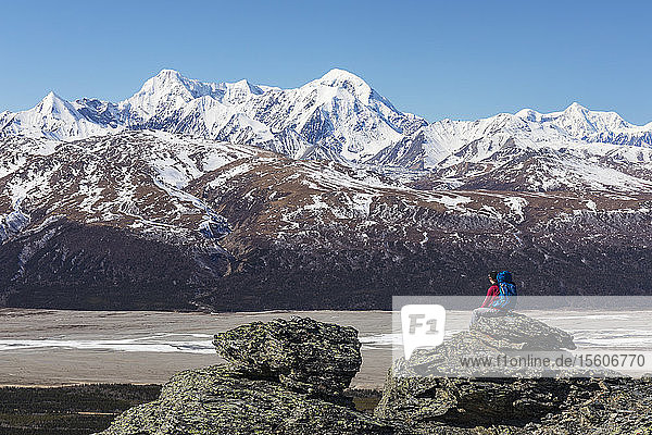A hiker takes in the view of McGinnis Peak  Mount Moffit  and Mount Hayes in the Eastern Alaska Range while resting on a rock overlooking the Delta River; Alaska  United States of America
