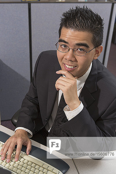 Happy Asian man with Autism working on computer in an office