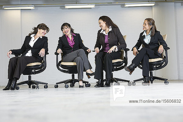 Business women laughing in office.
