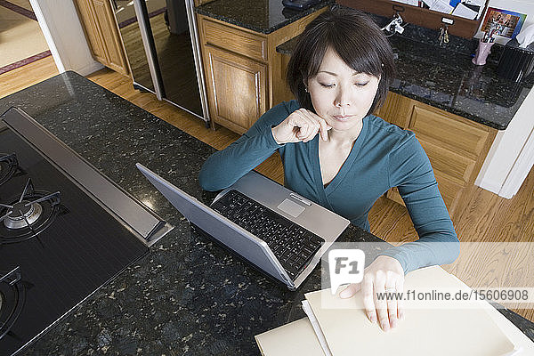High angle view of a mid adult woman sitting in front of a laptop and looking at documents