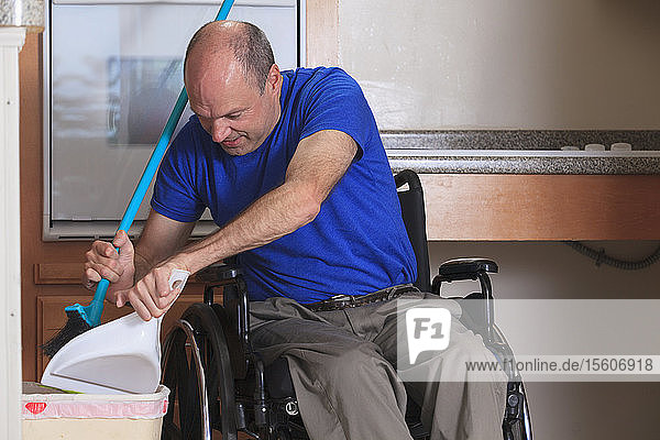 Man with Friedreich's Ataxia and deformed hands cleaning his house from his wheelchair with a broom