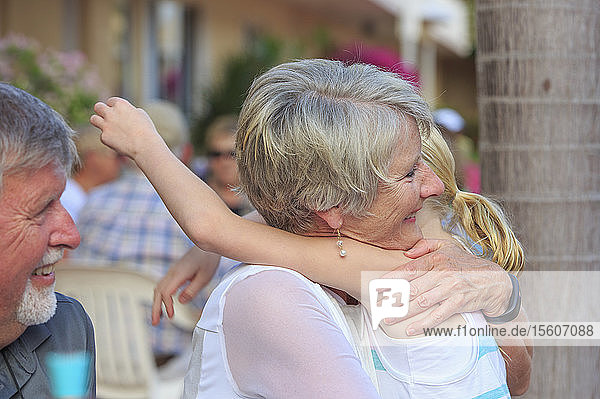 Loving grandparents and grandchild hugging