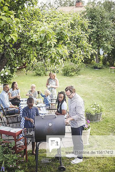 Schrägaufnahme eines Mannes  der mit einem Jungen einen Grill vorbereitet  während Familie und Freunde im Hinterhof am Tisch sitzen