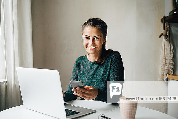 Portrait of smiling mid adult woman with mobile phone and laptop at table