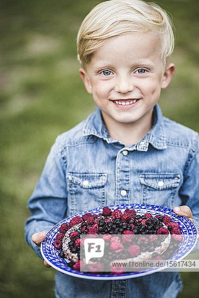 Porträt eines lächelnden Jungen mit Beerentorte im Garten