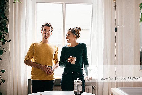 Glückliches Paar mit Kaffeetasse gegen Fenster zu Hause